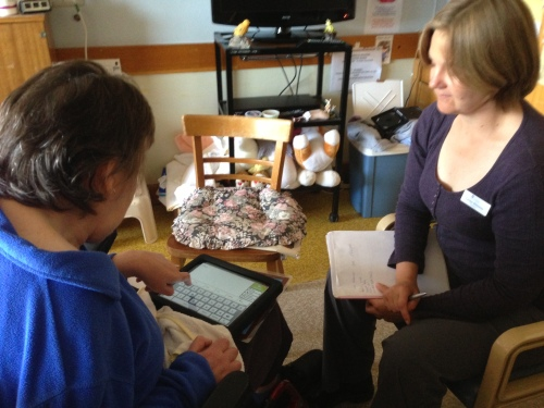 One of the participants in the trials of the iPads as assistive technologies undertaking training with research assistant Carolyn Bilsborow